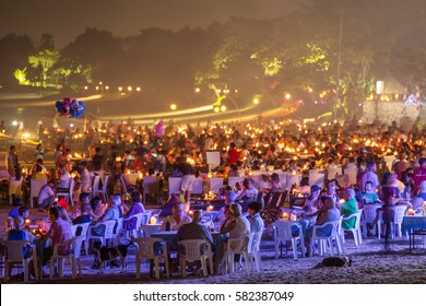 Bali, Indonesia - September 18, 2016: Tourists enjoy seafood dinners served on the beach in Jimbaran at night in Bali.