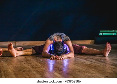 Bali, Indonesia - September 2017: Flexible Man in a Seated Forward Fold (Dragonfly Pose) Wearing Neon Headphones during a Silent Disco Event