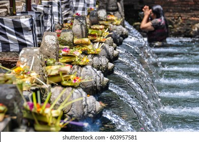BALI, INDONESIA - SEPTEMBER 27, 2012: Balinese woman taking purifying bath in the Tirta Empul Temple in Bali, Indonesia
