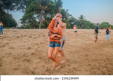 Bali, Indonesia - September 30, 2018: Caucasian Couple Salsa Dancing on the Beach during Silent Disco