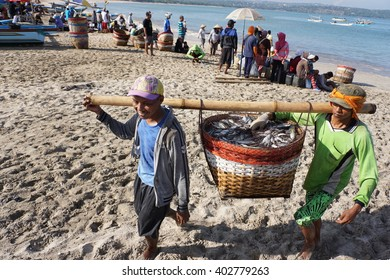 Bali, Indonesia-April 4, 2016:Unidentified fisherman carry fish baskets as they unload a catch from a boat at Jimbaran Beach, Bali, Indonesia.