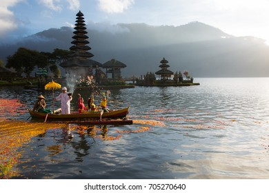 BALI INDONESIA-AUGUST 14,2017:CEREMONY ON THE POND WITH PAGODA BACKGROUND