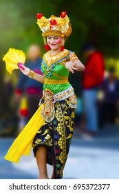 BALI ISLAND, INDONESIA - JUNE 28, 2017: Beautiful woman dressed in colorful sarong - Balinese style female dancer costume, dancing traditional temple dance Legong at Lovina beach square
