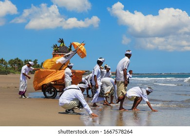 Bali Island, Indonesia - March 18, 2015: Balinese people procession walking by beach with hindu scared relics to ocean holy water for traditional ceremony Melasti before celebration silence day Nyepi