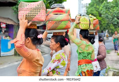 BALI - JAN 23: Unknown Indonesian women carry offerings in baskets on their heads in a procession to the village temple on Jan 23, 2012 in Ubud, Bali Indonesia.