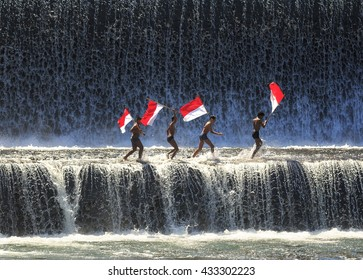 BALI - May 22 : Boys having fun and waving indonesian flag by playing water in an artificial dam on the Tukad Unda dam, Bali, Indonesia on May 22, 2014.