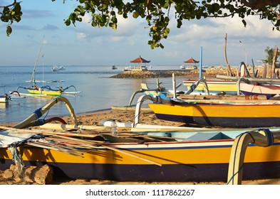 Bali Outrigger Fishing Boats and equipment resting on Sanur beach, Indonesia at dawn.