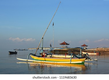 Bali Outrigger Fishing Boats and a Glass Bottom tourist boat moored off Sanur beach, Indonesia at dawn.