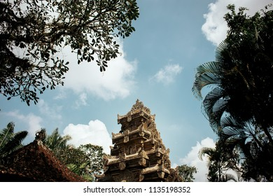 Bali temple framed by tress against blue sky