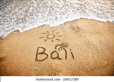 Bali title with sun and palm drawing on the sand beach near the ocean