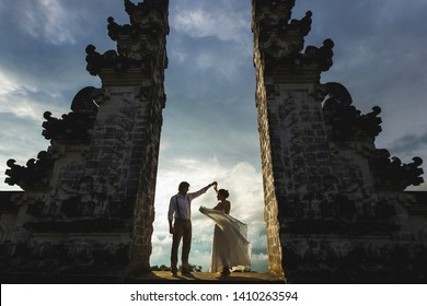 Bali Travel concept. Balinese famous symbol - traditional gate in temple. Welcome in Bali. Couple in love at sunset.
