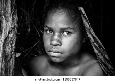 Baliem Valley, West Papua, Indonesia- November 11 2016: Portrait of a young  black girl from the Dugum Dani tribe in a small village in West Papua, Indonesia.