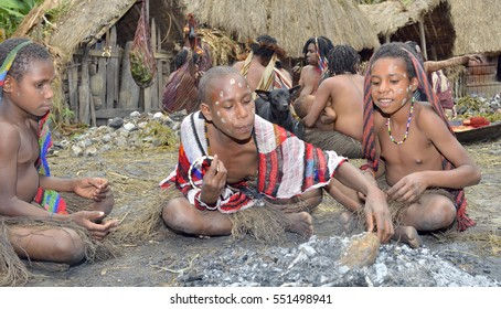 BALIEM VALLEY, WEST PAPUA, INDONESIA, MAY 16th, 2016: Dugum Dani tribe people. Unidentified children of Dugum Dani tribe cook food in fire. Small village on 16, May 2016 in West Papua, Indonesia.