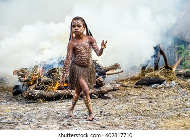 BALIEM VALLEY, WEST PAPUA, INDONESIA, MAY 16th, 2016: Dugum Dani tribe. Unidentified child of Dugum Dani tribe is near the fire in the smoke. 16, May 2016 in West Papua, Indonesia.