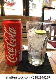 BALI,INDONESIA - SEPT 9, 2018: Original glass and can of Coca Cola drink with ice on wooden background. The drink is produced and manufactured by The Coca-Cola Company.