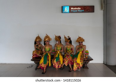 BALI/INDONESIA-APRIL 30 2019: five female Balinese dancers were sitting resting on long chairs after performing on stage. They chat with each other and use their cellphones for selfie and chatting