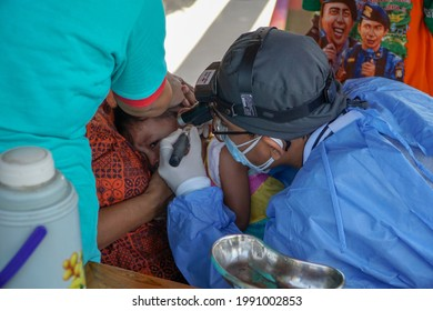 BALI,INDONESIA-JUN 14 2021: An ENT doctor is examining the ears, nose and throat of a pediatric patient. ENT examinations are very risky because they come into direct contact with patients