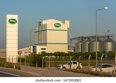 Balikesir / Turkey - July, 27, 2019: Sutas Dairy Plant Building, landscape gardening, trees and Raw Material Storage Tanks image taken from the road.