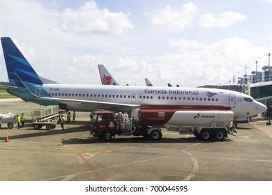BALIKPAPAN, INDONESIA - AUGUST 02, 2017 : Pertamina Truck parked near Garuda Indonesia Boeing 737-800NG, Ground staff loading baggage to cargo bay at Sultan Aji Muhammad Sulaiman Airport Sepinggan.