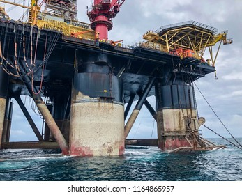 Balikpapan, Indonesia - August 2018: Semi submersible drilling rig view from crew vessel's deck. Rig deballasted so legs can be seen at all heights including the anchor rack