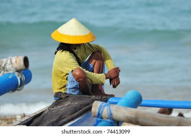 A Balinese fisher man sitting on a fishing boat on the beach
