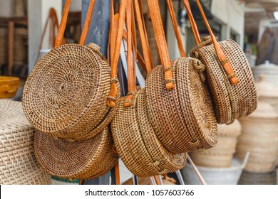 Balinese handmade rattan woven round shoulder bags with leather handles at a street shop. Bali, Indonesia.