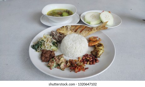 Balinese mixed rice containing of fried fish, fish soup, shrimp, squid, vegetable and sambal. This food also called Nasi Campur Bali.