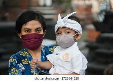 Balinese mother and child are wearing traditional clothes during the corona pandemic or covid-19. They both use masks to protect themselves from virus attacks. They prepare to pray at the temple