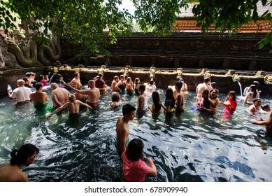 Balinese people in holy spring water of sacred pool at Pura Tirta Empul Temple, Tampaksiring, Bali, Indonesia, 27 June 2017.
