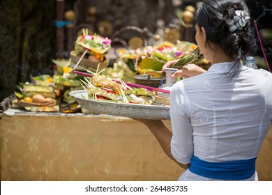 Balinese  woman carrying offering to local temple in Bali, Indonesia. Offering flowers and other gifts is very popular tradition on Bali.