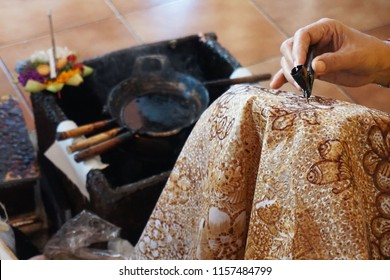 Balinese woman drawing batik pattern on white fabric