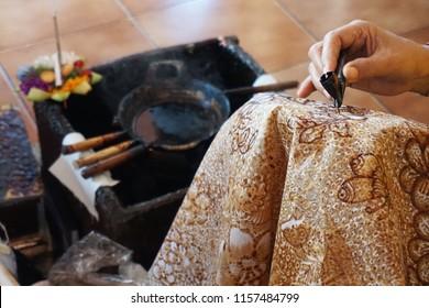 Balinese woman drawing batik pattern