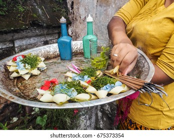balinese woman holding a tray with offerings and new canang sari, Ubud, Bali