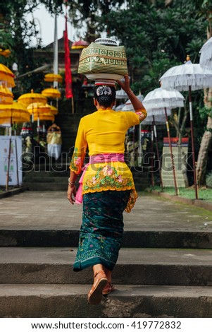 Balinese woman in traditional clothes carrying ceremonial box with offerings on her head during Balinese New Year celebrations on March 03, 2016 in Ubud, Bali.