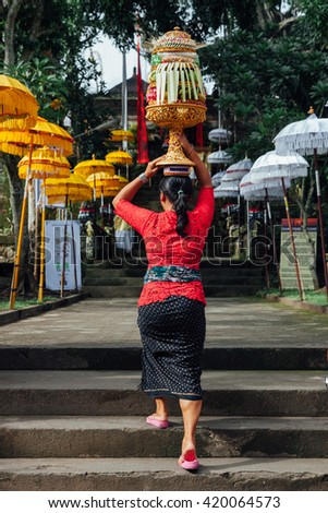 Balinese woman in traditional clothes  carrying ceremonial offerings on her head during Balinese New Year or Nyepi Day celebrations in Ubud, Bali.