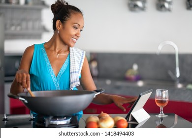 Balinese woman using a tablet computer to cook in her kitchen