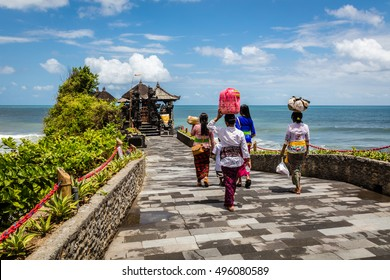 Balinese women carrying baskets with offerings to a temple at Pura Tanah Lot, Bali Island, Indonesia