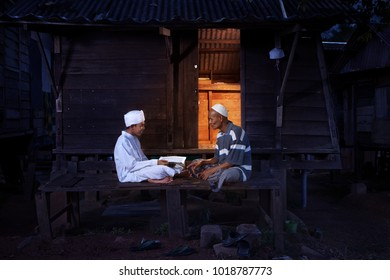 BALING,MALAYSIA - NOVEMBER 18TH 2016 : Father teaching son to recite the Quran.