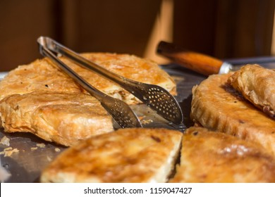 Balkan burek with cheese with food catcher in bakery shop. Traditional pie breakfast in the Balkans concept. Close up, selective focus