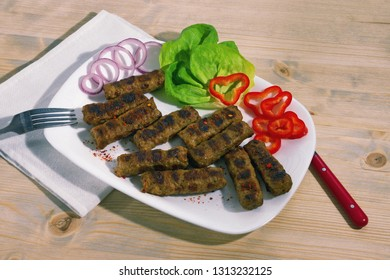 Balkan cuisine. Cevapi - grilled dish of minced meat- with vegetables on white plate