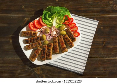 Balkan cuisine. Cevapi - grilled dish of minced meat- with vegetables. Dark rustic background. Flat lay
