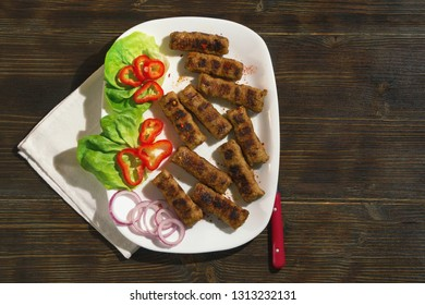 Balkan cuisine. Cevapi - grilled dish of minced meat  - with vegetables on a white plate. Dark rustic background, flat lay, free space for text