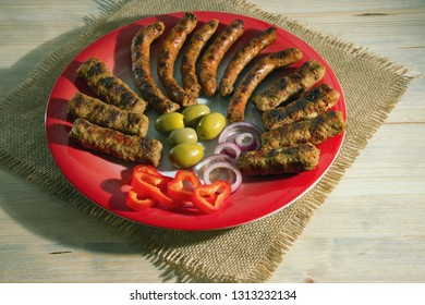 Balkan cuisine. Cevapi and kobasica - grilled dish of minced meat - on red plate, rustic background