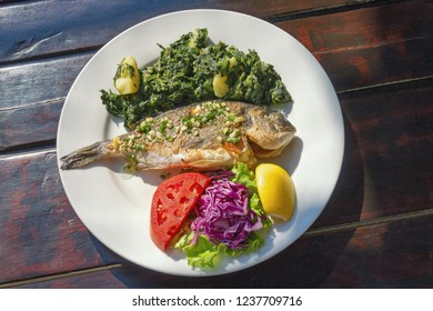 Balkan cuisine. Grilled fish ( sea bream ) with vegetables and slice of lemon on white plate. Dark rustic background, flat lay