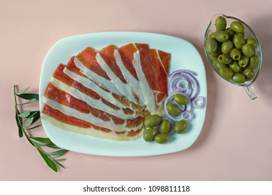 Balkan cuisine . White plate with slices of prsut (dry-cured ham,  prosciutto)  and green olives on pink pastel background, flat lay