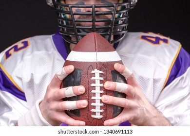 Ball for American football in front of footballer face, close up portrait.