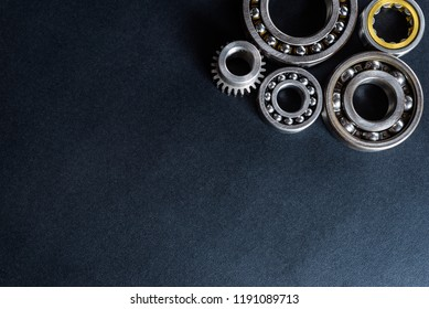 Ball bearing lying on a black background, flat view from above.