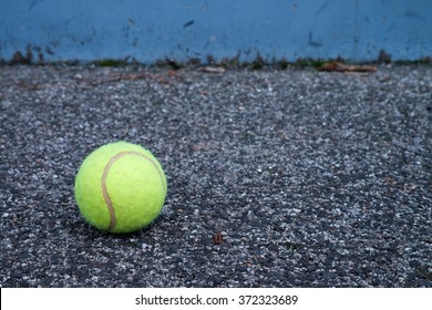 Ball beside tennis training wall. Empty training tennis court, end of outside season.