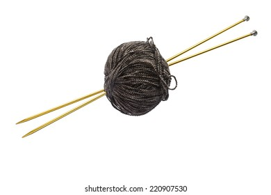 Ball of brown yarn on golden metal knitting needles isolated over white