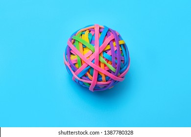 A ball of colored rubber bands on a blue background